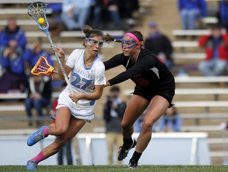 Aly Messinger (27) muscles her way past a Florida defender on Saturday at Fetzer Field. The Tar Heels won 20-8.