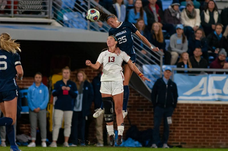 USC's junior forward Tara McKeown (13) goes up against UNC's freshman defender Maycee Bell (25) during the NCAA quarterfinal game at Dorrance Field on Friday, November 29, 2019. Bell scored the game winning goal against USC for a final score of 3-2.
