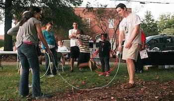 """Hana Haidar, 19, a sophomore English major from Chapel Hill, and Duncan Dorris, 20, a sophomore biology major from Asheville, play jump rope with 4-year-old Isaiah Alston at Hillsborough Night Out. Haidar and Dorris are part of UNC's Habitat for Humanity Community Outreach and Advocacy committee. """"We want to connect with the community beyond building houses,"""" Haidar said."""