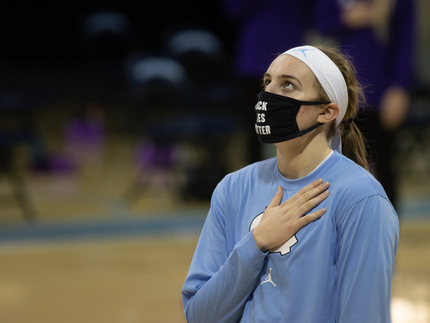 UNC first year forward Alyssa Utsby (1) places her hand over her heart during the national anthem prior to Carolina's 95-70 victory over High Point, November 29, 2020.