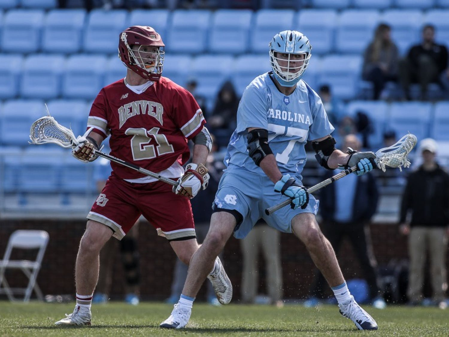 UNC junior midfielder Tanner Cook (77) fends the ball from Denver junior midfielder Kyle Smith (21) during UNC's 12-10 home loss against the University of Denver on Saturday, March 3, 2019 at the UNC Soccer and Lacrosse Stadium in Chapel Hill, N.C. This was the UNC Men's Lacrosse team's inaugural game at the UNC Soccer and Lacrosse Stadium.