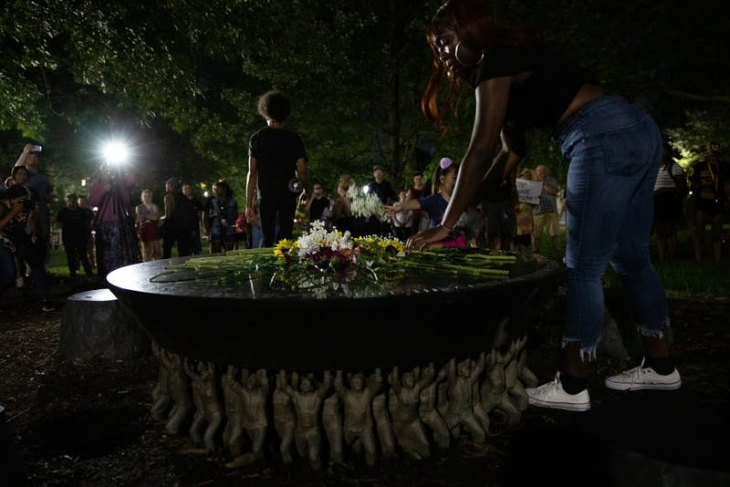 "Students lay flowers on the Unsung Founders Memorial in McCorkle Place as part of a celebration of the one-year anniversary of the toppling of Silent Sam on August 20, 2019. Speakers at the event remarked on the alleged shortcomings of the University in ""reckoning"" with its history."