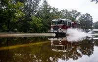 A Carrboro fire truck drives through a flooded section of N. Greensboro St. on Monday morning. Parts of Carrboro and Chapel Hill experienced flash flooding Monday after feeling minimal effects from Hurricane Florence last week.