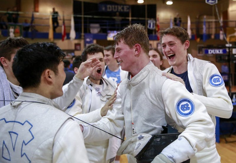 The UNC men's fencing team celebrates James Mulligan's victory over Boston College at the men's fencing match in Card Gym at Duke University on Saturday, Feb. 9 2018.
