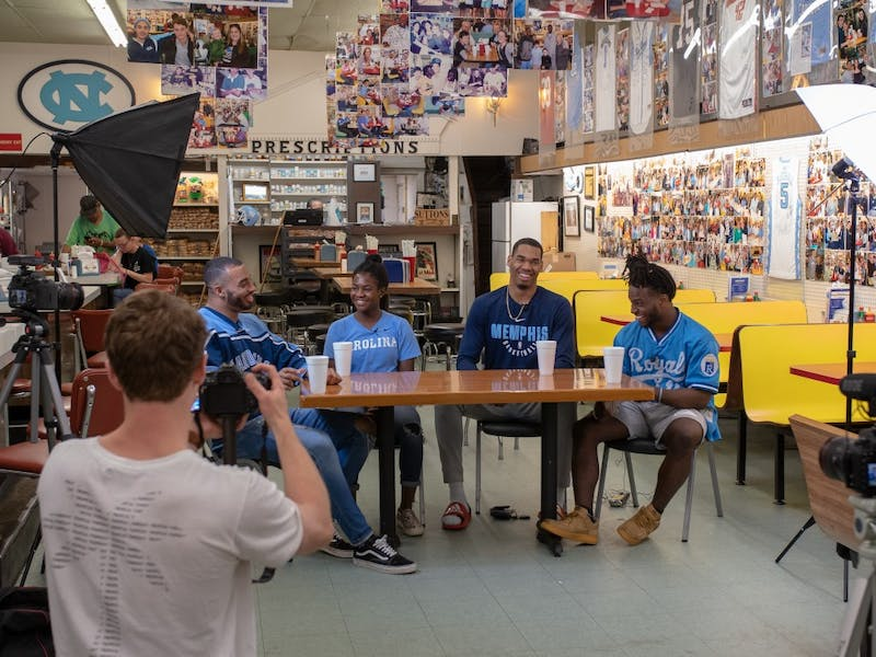 Sophomore Luke Buxton films as (from left to right) Jake Lawler, Brianna Pinto, Garrison Brooks and Michael Carter talk about life as black student-athletes at UNC for the student-produced show UNCUT filmed at Sutton's Drug Store. Photo courtesy of Kenan Reed.