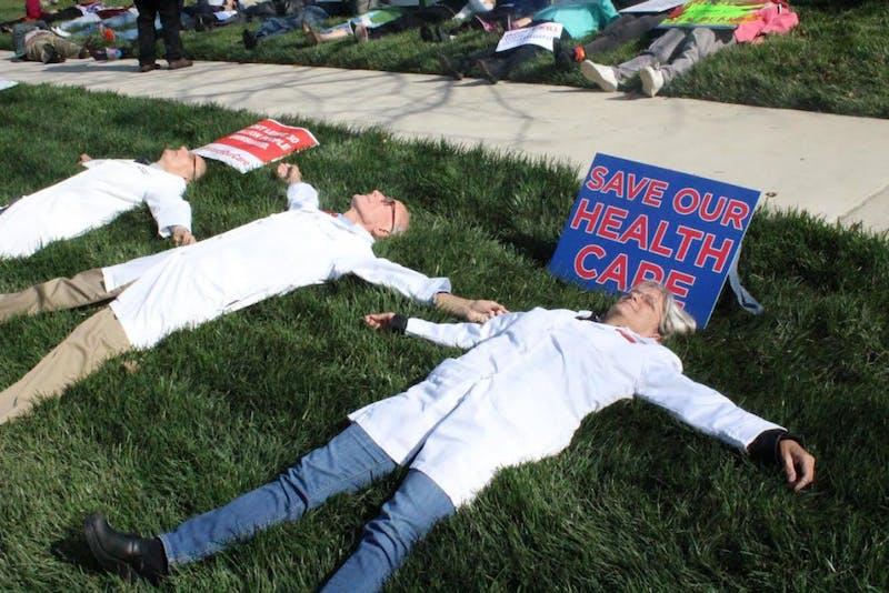 Participants spread out in the grass during Friday's die-in in Durham in reaction to the possible changes in health care policies.