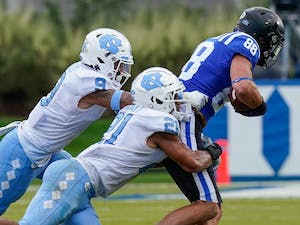 UNC linebacker Chazz Surratt (21) and defensive back Cam'Ron Kelly (9) tackle Duke tight end Jake Marwede (88) during the second half of the game at Wallace Wade Stadium on Saturday, Nov. 6, 2020. Photo courtesy of Jim Dedmon/Pool Photo-USA TODAY Sports