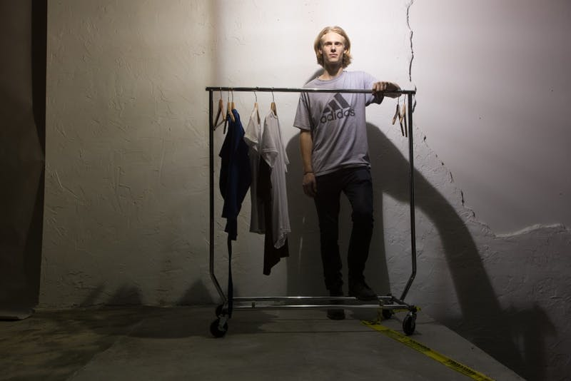 James Creissen, a sophomore business major, poses in front of a rack of clothes he designed. Creissen held a fashion show on East Rosemary Street Thursday night.