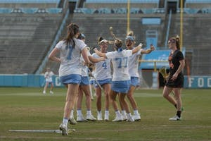 The North Carolina women's lacrosse team swarms sophomore Olivia Ferrucci (77) after her game-winning goal against Virginia Tech on March 28 at Kenan Stadium.