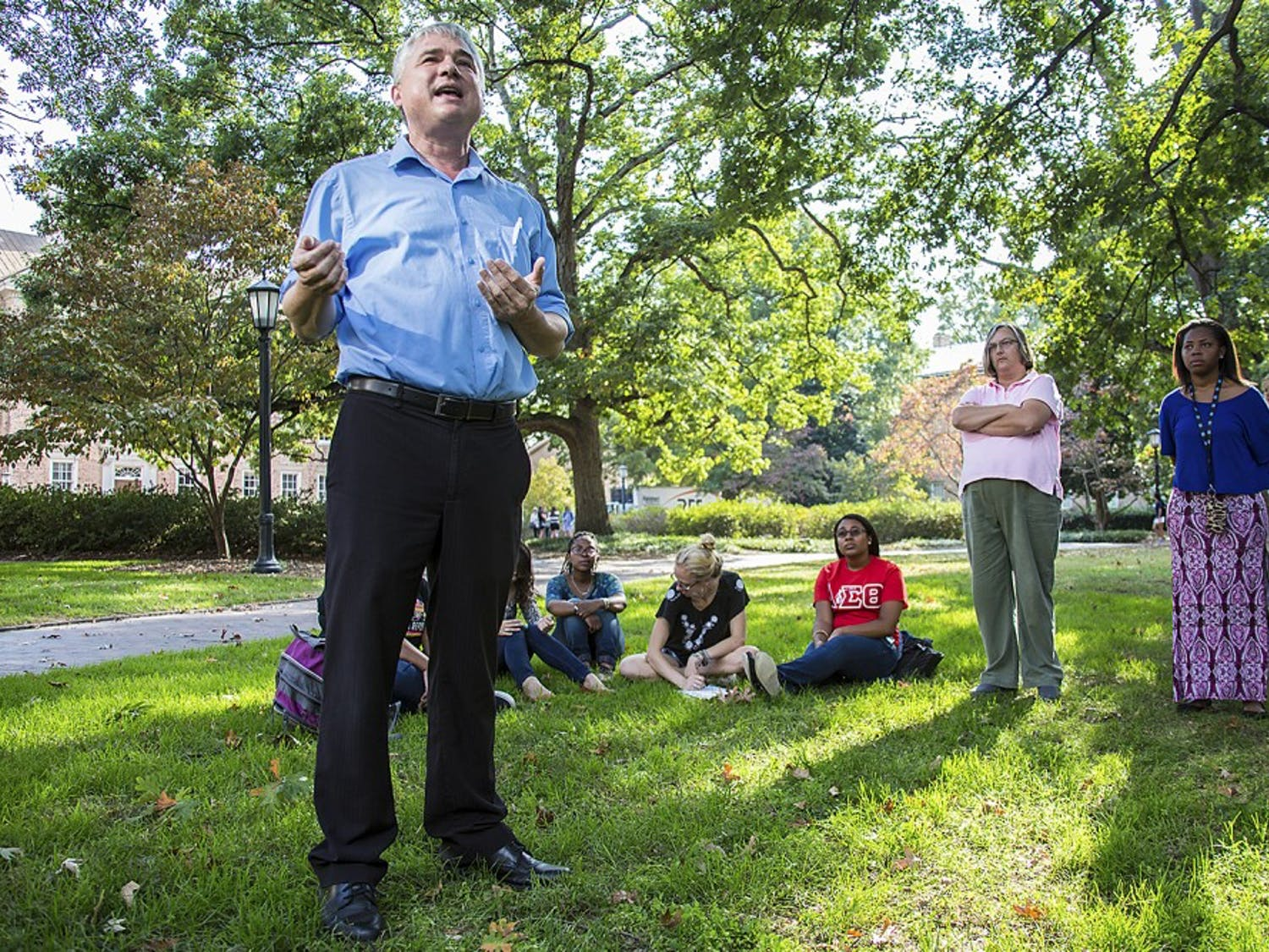 Tim McMillan, senior lecturer in UNC's Department of African, African-American and Diaspora Studies, talks to students and local residents on the Black and Blue Tour about historical landmarks on campus related to UNC's racial history.