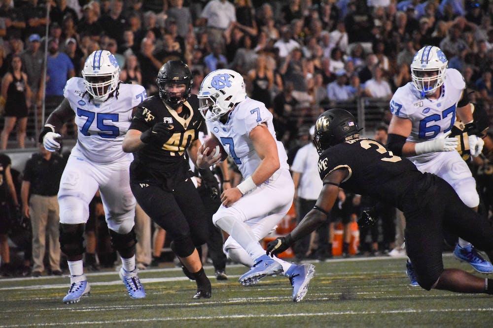 <p>UNC-Chapel Hill freshman quarterback Sam Howell (7) runs the football Friday, September 13, 2019.&nbsp;</p>
