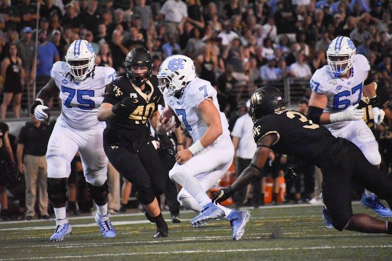 UNC-Chapel Hill freshman quarterback Sam Howell (7) runs the football Friday, September 13, 2019.