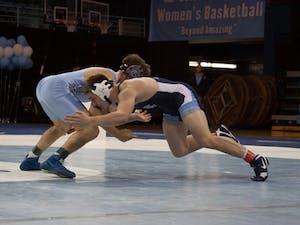 First year Austin O'Connor (in navy) wrestles senior teammate Troy Heilmann during UNC's wrestle-offs on Friday night in Carmichael Arena.