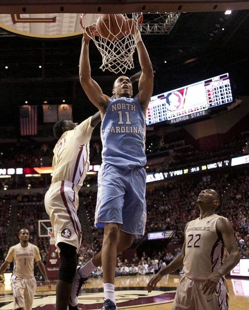 North Carolina's Brice Johnson (11) dunks for two of his career high 39 points over Florida State's Chris Koumadje (21) and Xavier Rathan-Mayes (22) on Monday, Jan. 4, 2016, at the Tucker Center in Tallahassee, Fla. (Robert Willett/Raleigh News & Observer/TNS)