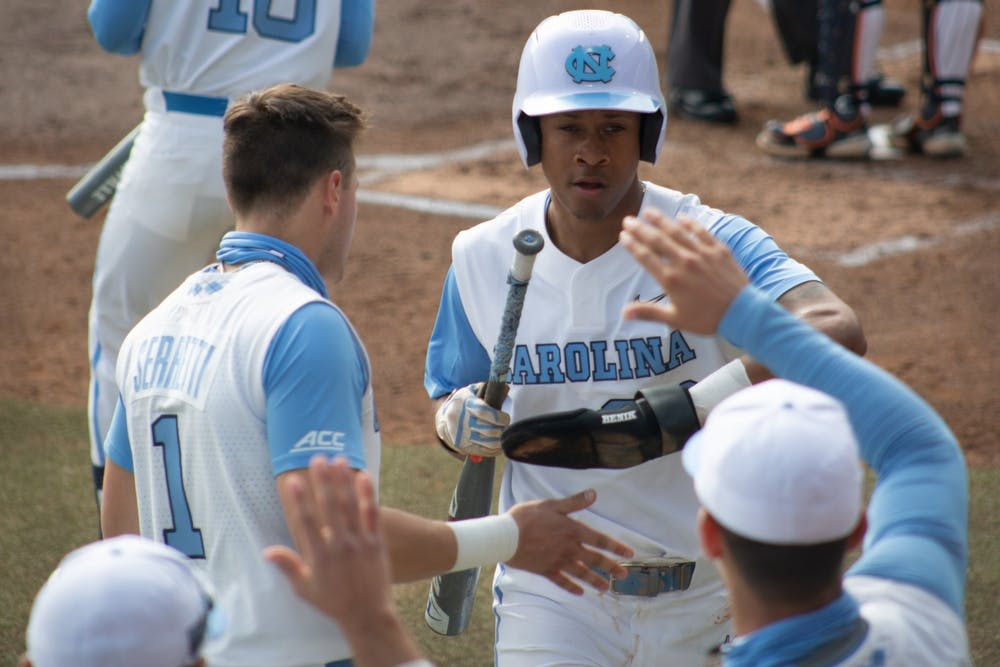 Sophomore outfielder Justice Thompson (20) gets high fives from teammates after stealing home against University of Virginia on Saturday, Feb. 27, 2021. The Tar Heels beat the Cavliers 2-1.