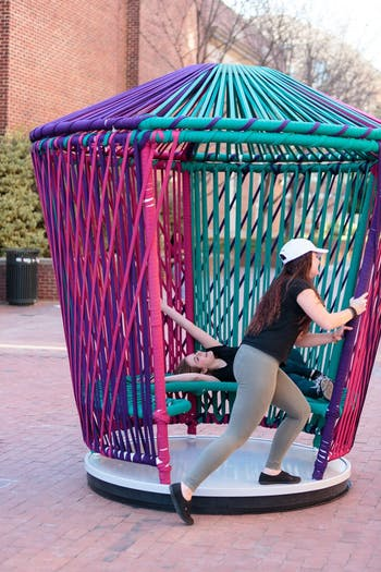 First year dramatic art and journalism major  Amy Cockerham (left) and first year psychology major Madison Robertson spin on one of the new structures outside Davis library.