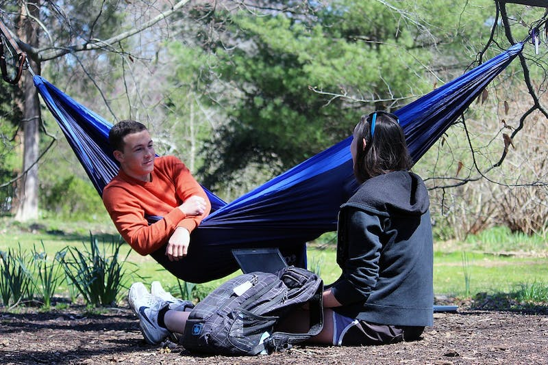 Patrick O'Neill, a sophomore business major, sits in his hammock in the Arboretum on Monday afternoon with Rachel Helms, a junior psychology major.