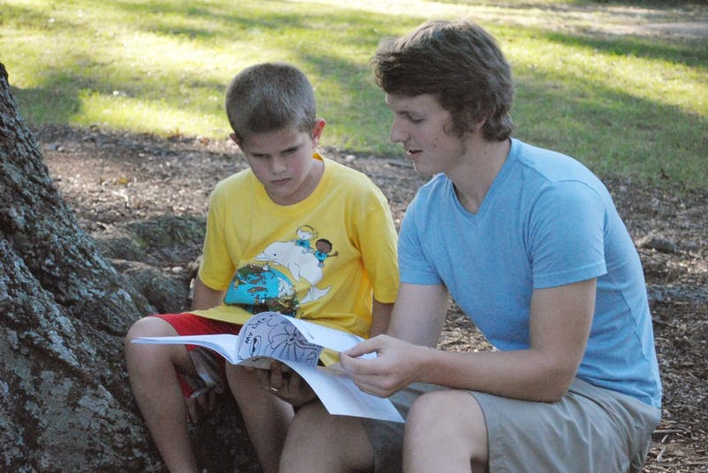 """Jake King, who produced a lot of the artwork for the """"My Life As A Plant"""" coloring workbook, explains some of the content to Peter Dunson, age 7."""