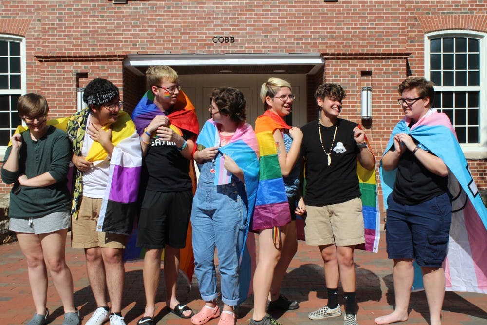 A group of students stand in front of Cobb Community on Sunday, Sept. 28, 2019. They hold flags for different groups within the LGBTQ+ community.