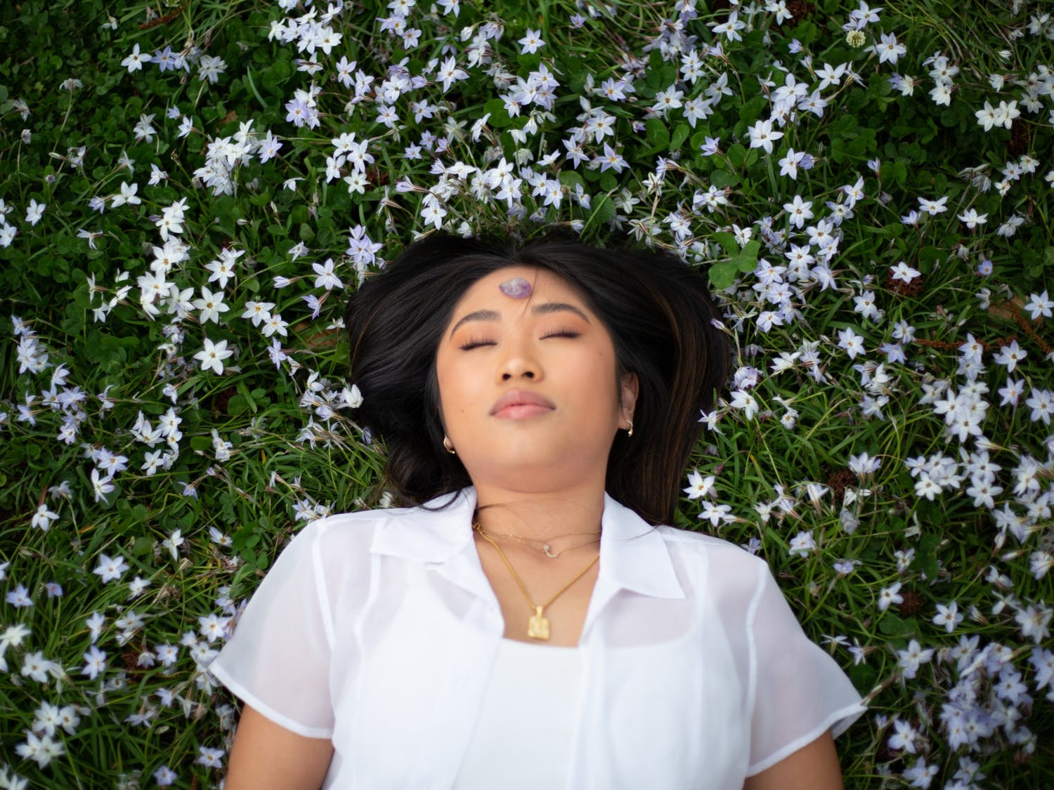 Junior Advertising and Public Relations major Tran Nguyen meditates with her crystals in the Coker Arboretum on Thursday, Apr. 1, 2021.