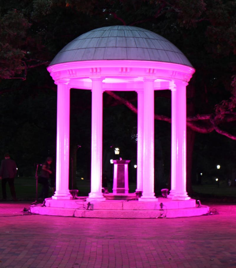 The Old Well stands illuminated with pink lights for the first time in honor of Breast Cancer Awareness month during the Pink out Polk Place event put on by the UNC Lineberger Comprehensive Cancer Center. The event included a fun run where the first 100 runners were covered in pink and blue powder.