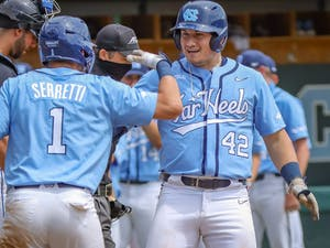 UNC graduate first baseman and outfielder Brett Centracchio (42) celebrates his home run with UNC sophomore shortstop Danny Serretti (1) during the Tar Heels' 11-5 win against Duke on Sunday, April 11, 2021 in Boshamer Stadium.