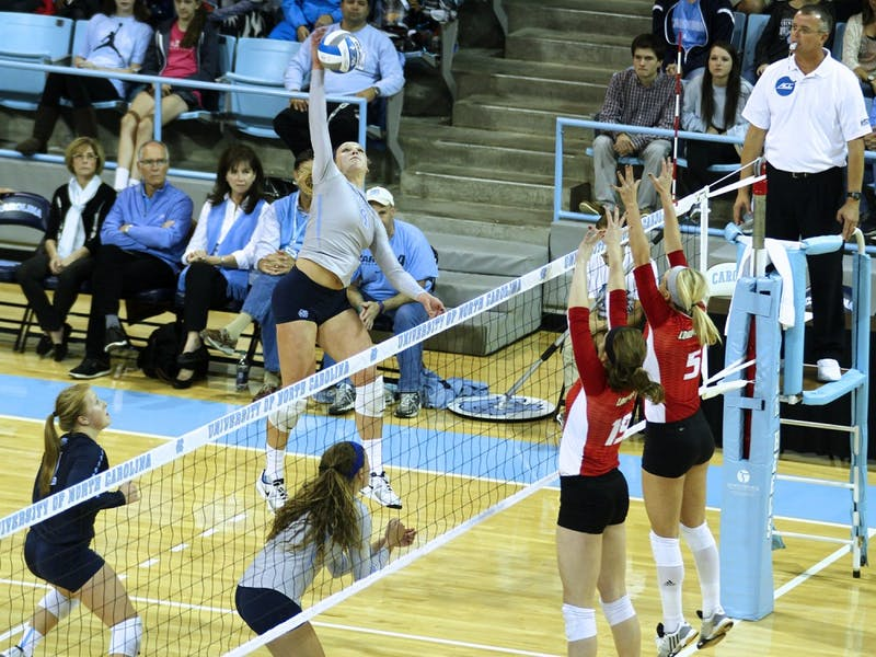 Tar Heel Leigh Andrew (4) taps the ball over the net against Louisville Friday night.