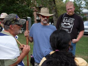 Lance Spivey (middle), Howard Snow (left) and other members of the Heirs to the Confederacy talk to a student counterprotester on Aug. 20. Photo courtesy of Twitter user @m152375.