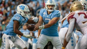 UNC junior quarterback Sam Howell (7) hands the ball off graduate running back Ty Chandler (19) during the Tar Heels' home football game in Kena Stadium on Oct. 9 against the Florida State Seminoles. FSU won 35-25.
