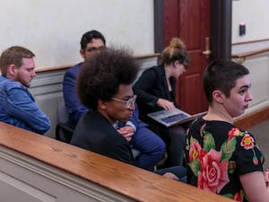 (From left) Shawn Birchfield-Fin, Jonathan Fuller and Lauren Aucoin watch the replay of news footage from the toppling of Silent Sam during their trial at the Orange County Courthouse in Hillsborough, N.C. on Thursday, April 25 2019.