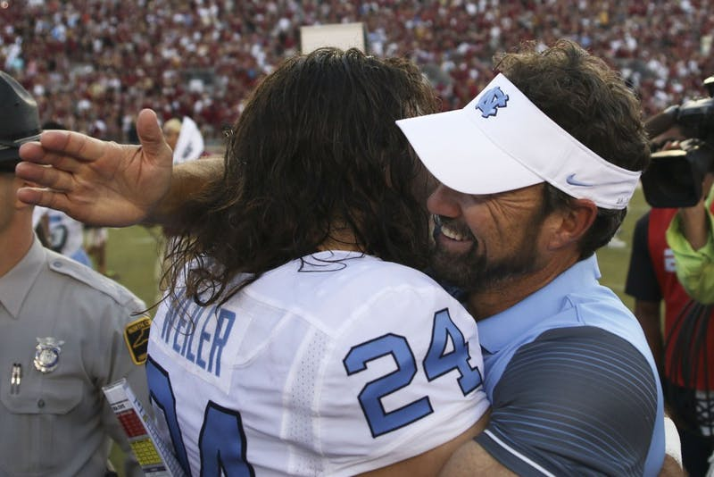 UNC kicker Nick Weiler (24) embraces head coach Larry Fedora after the team's dramatic win over Florida State.