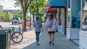 Two students walk on Franklin Street in Chapel Hill on April 13, 2021