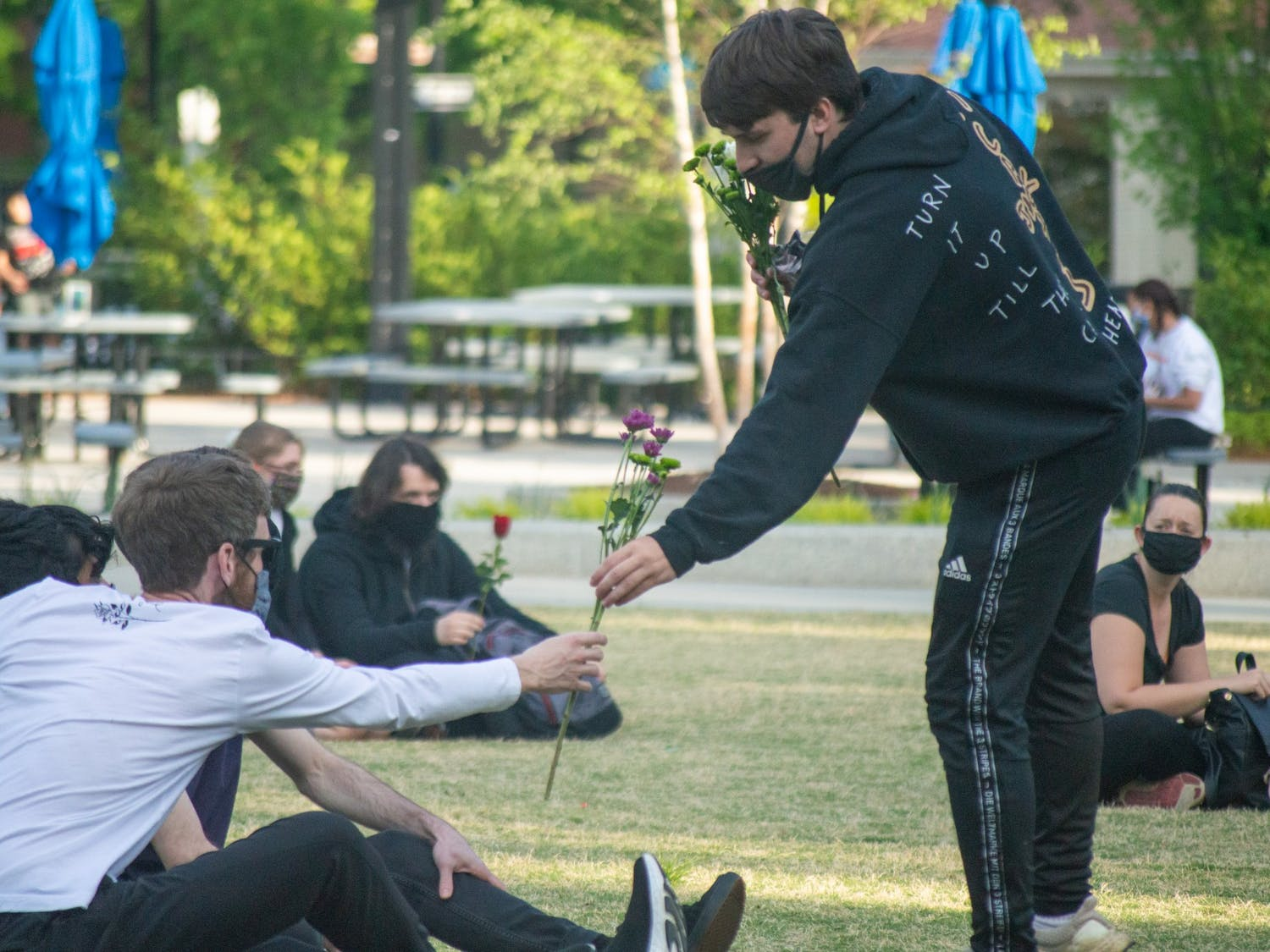 A volunteer at a community organized vigil in memory of Daunte Wright and Jaida Peterson hands out flowers. The vigil took place in Moore Square Park in downtown Raleigh on Sunday Apr. 18, 2021.