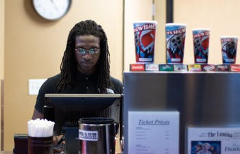 Akin Dunston of Carrboro works the front desk at the Lumina theater in Chapel Hill. The Lumina recently announced that it would not be closing after reporting that it would.