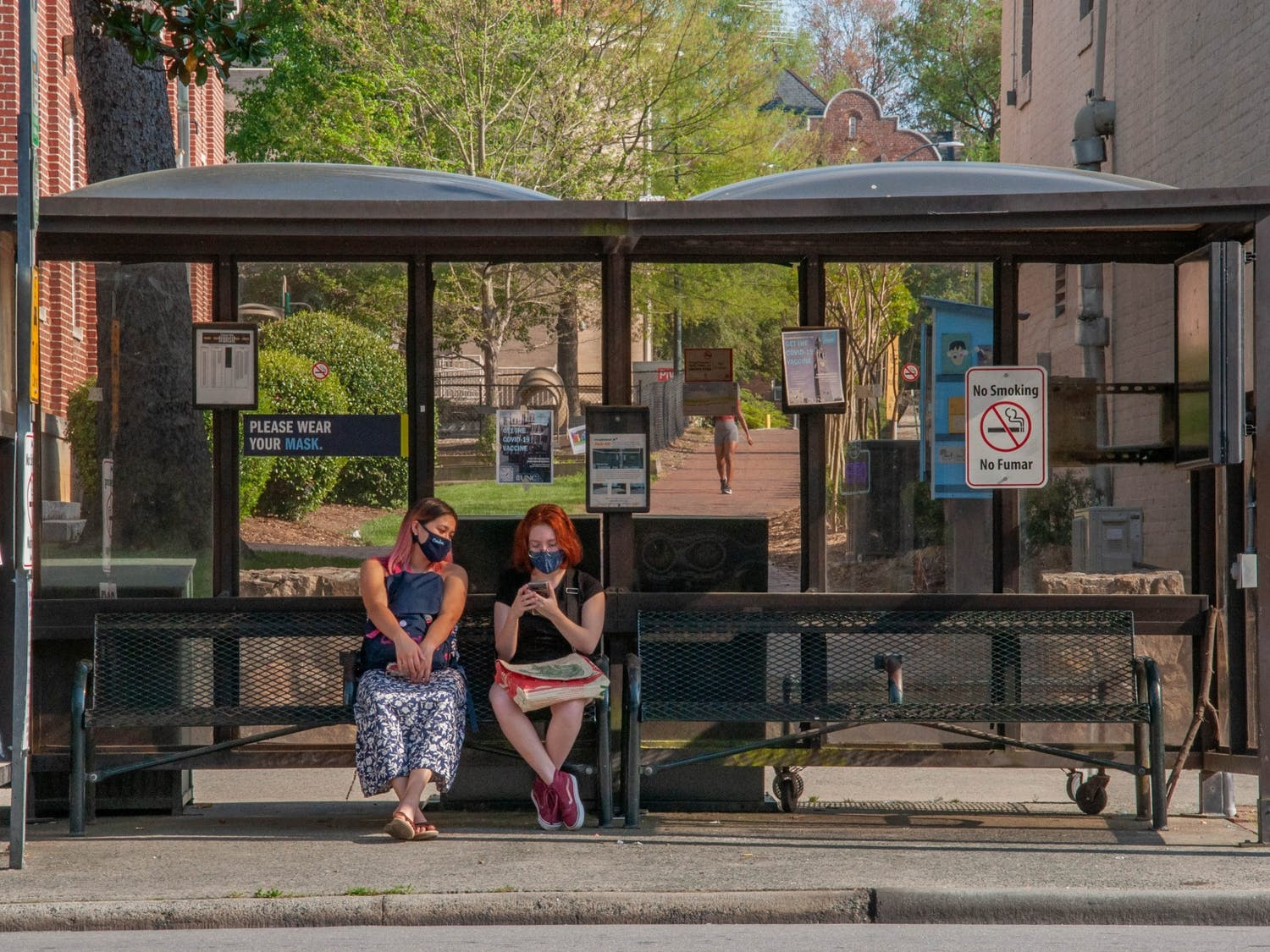 Two students sit at the bus stop on Franklin Street in Chapel Hill on April 13, 2021.