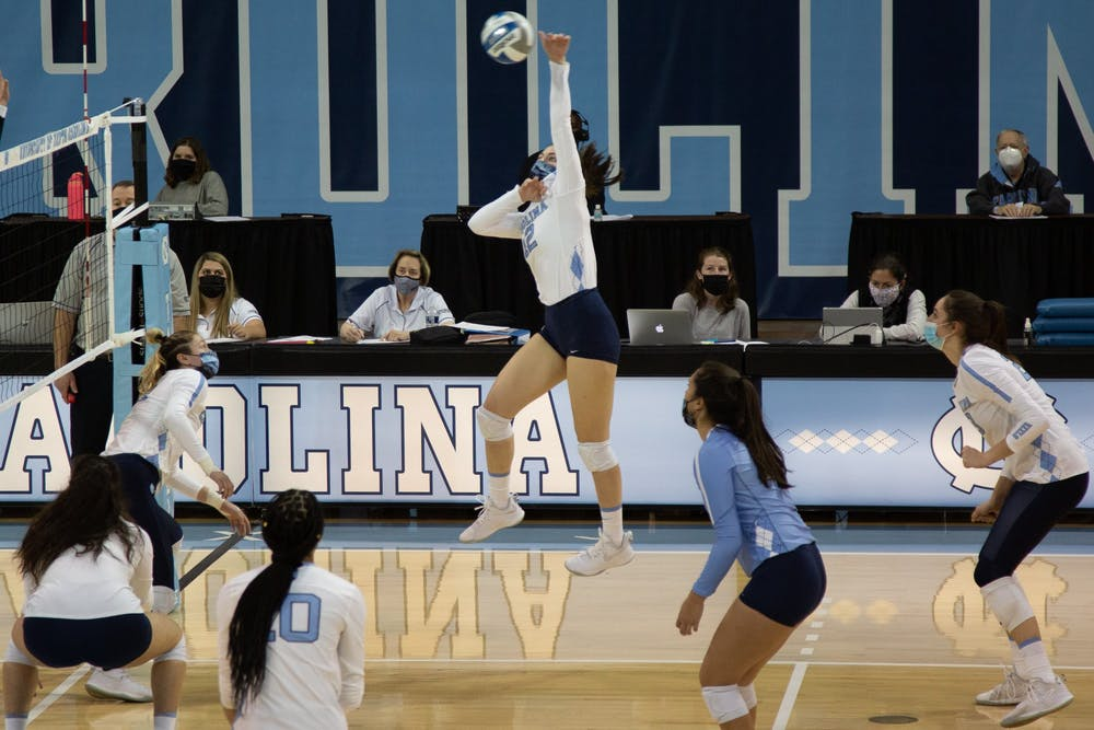 Junior setter Erin Boone (12) hits the ball in a volleyball game against Appalachian State University on Thursday, Feb. 18, 2021 in Carmichael Arena. The Tar Heels won 3-0.