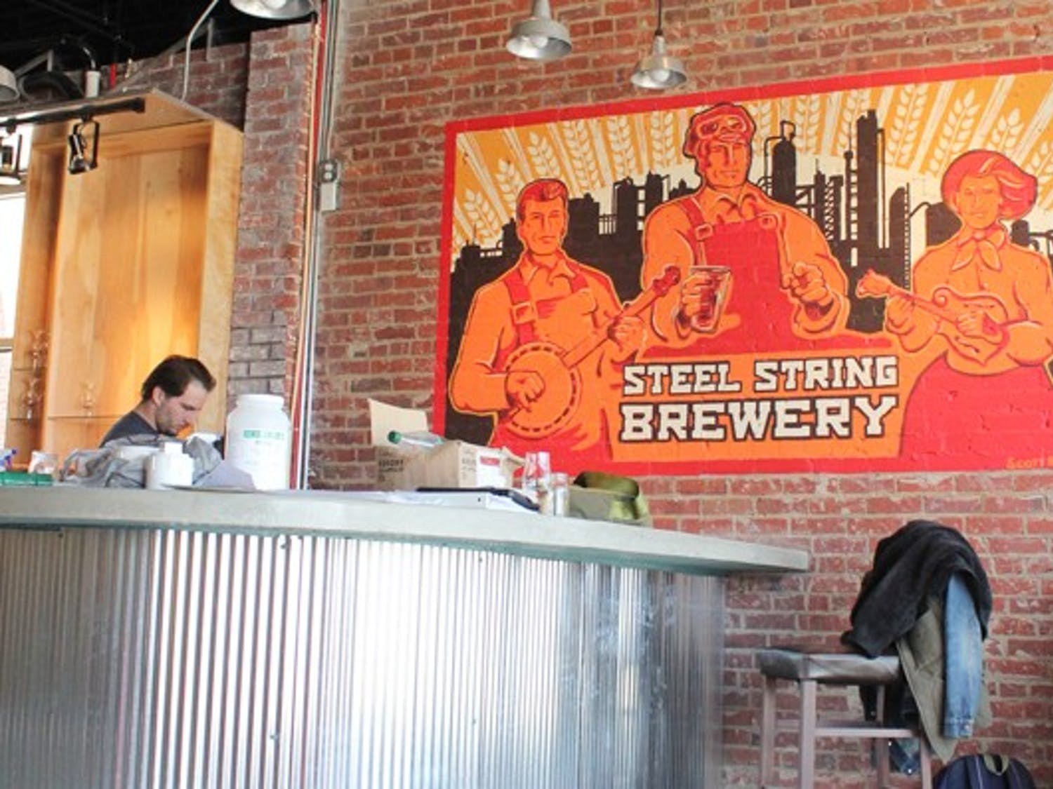 """Eric Knight (blue plaid shirt and glasses), Hoopla Czar, and Andrew Scharfenberg (not in any pictures), Logistics Czar, work in Steel String Brewery in Carrboro, which they are opening. """"Yeah, we decided not to be boring,"""" Knight said in regards to their position titles."""