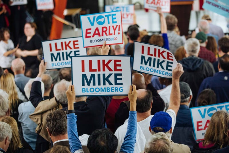 Supporters wave signs as Michael Bloomberg addresses the crowd during an early voting rally at Raleigh Union Station on Thursday, Feb. 13, 2020, in Raleigh, North Carolina. The rally marked the start of early voting in North Carolina for the March 3 Super Tuesday primary elections. (Kevin Hagen/Mike Bloomberg 2020).