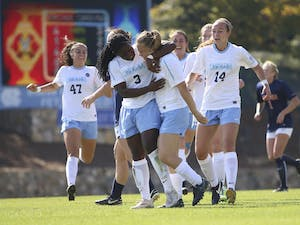 The women's soccer team celebrates after Madison Schultz (1) scored against Virginia on Sunday.