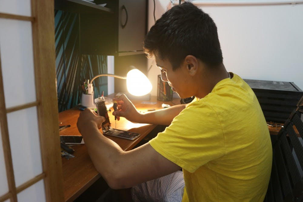<p>Juan Pablo works on a cellphone at his electronic repair store in Chapel Hill</p>