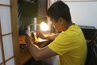 Juan Pablo works on a cellphone at his electronic repair store in Chapel Hill
