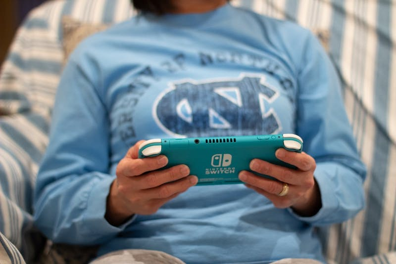 DTH Photo Illustration. A woman plays a Nintendo Switch Lite.