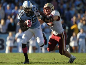 Former UNC tight end Eric Ebron attempts to shake off a Boston College defender in 2013.