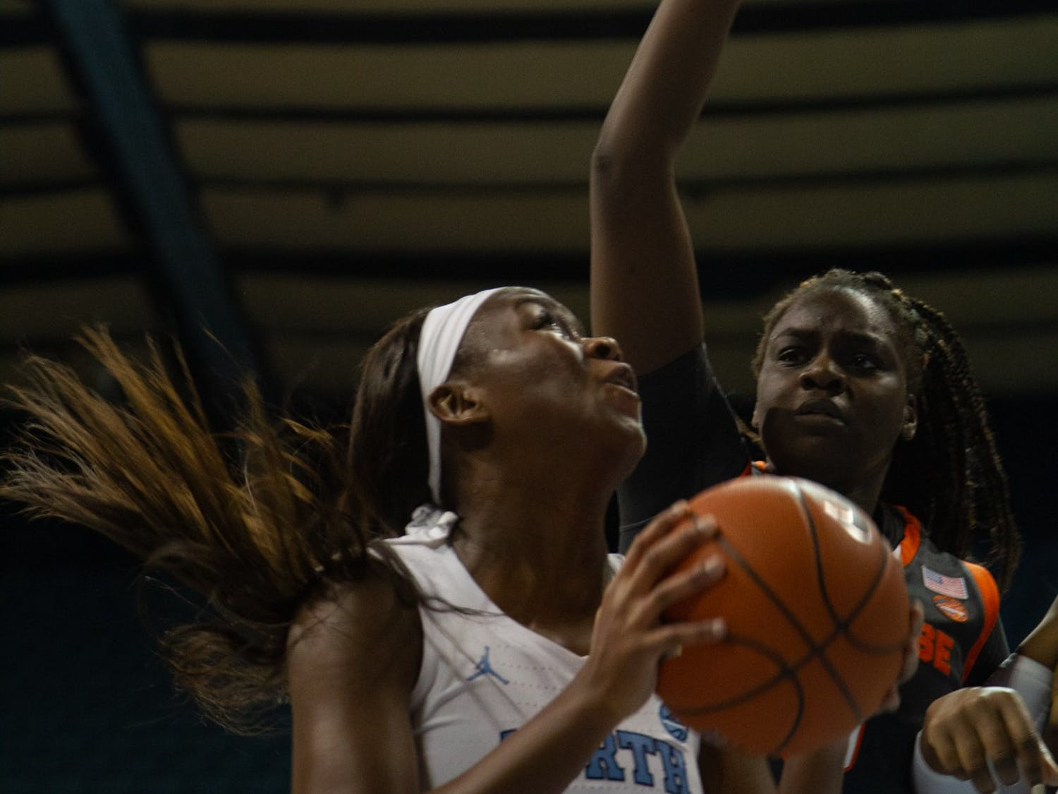 UNC first-year forward Malu Tshitenge (21) goes up for a shot while Syracuse attempts to block during a game in Carmichael Arena on Thursday, Feb. 13, 2020. The Orange beat the Tar Heels 74-56.