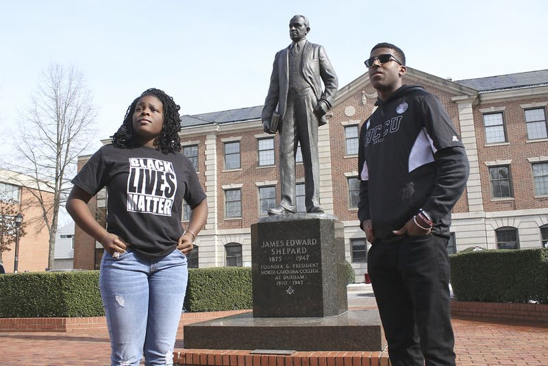 Raven Cheatham, a physical education major and Ajamu Dillahunt, a political science and history double major, both first-years at NC Central University, discuss their work as student activists. Cheatham and Dillahunt pose in front of the statue of James Shepard, founder of NCCU.