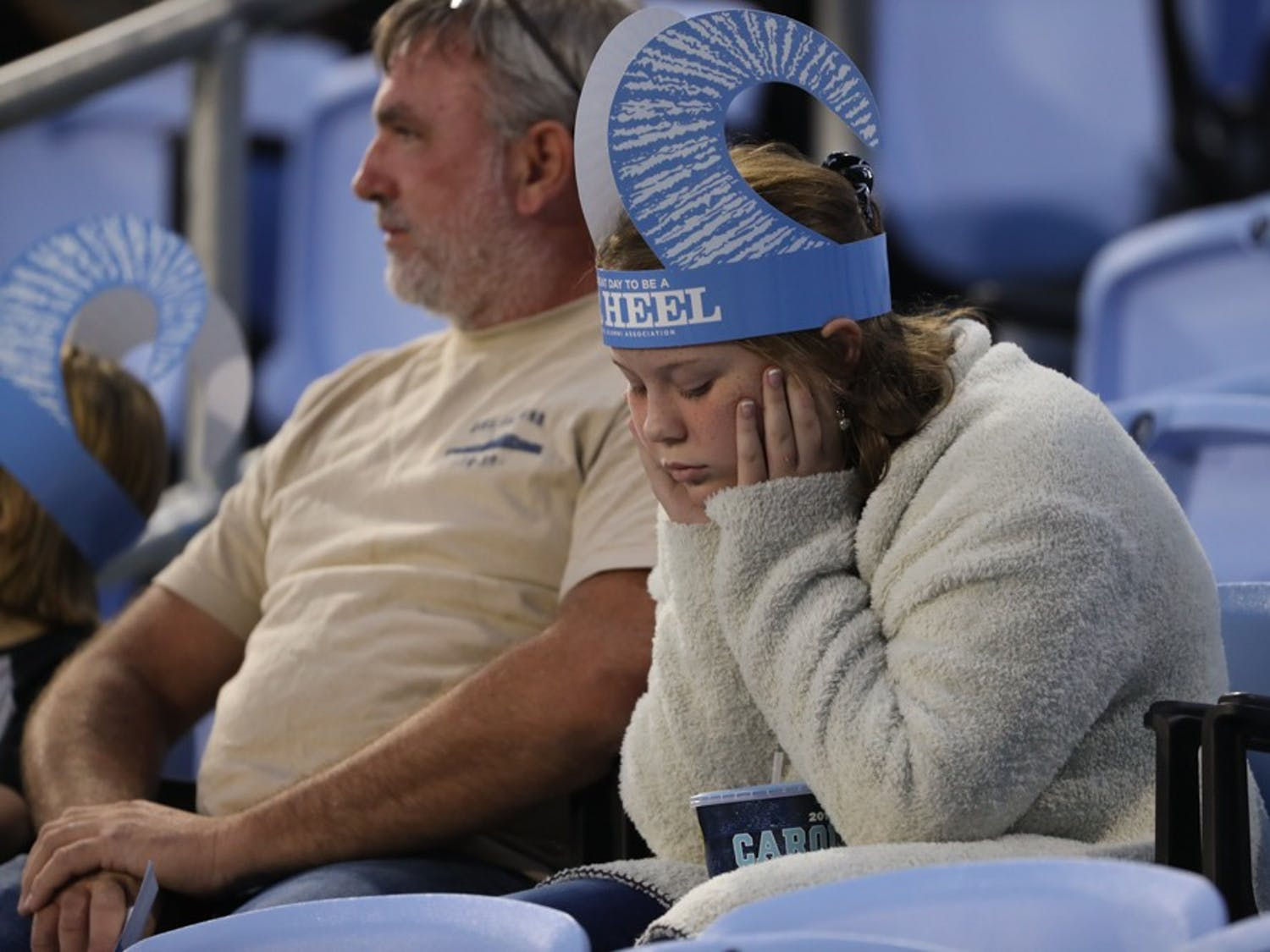 A young fan of UNC Men's Soccer team sits in disappointment after the crucial loss on Senior Day.