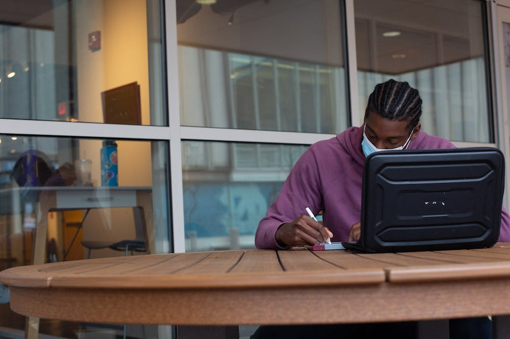 Junior Kobe Spells sits outside the Union doing coursework on March 18, 2021.