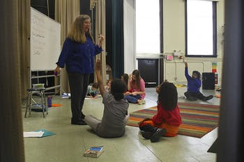 Jenny Justice, the artistic director of Hamlet Project in Durham, does vocal exercises with students in the E.K. Powe Elementary School  auditorium.