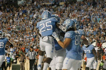 Javonte Williams celebrates a first-quarter touchdown during last Saturday's game versus Miami. The Tar Heels won, 28-25.