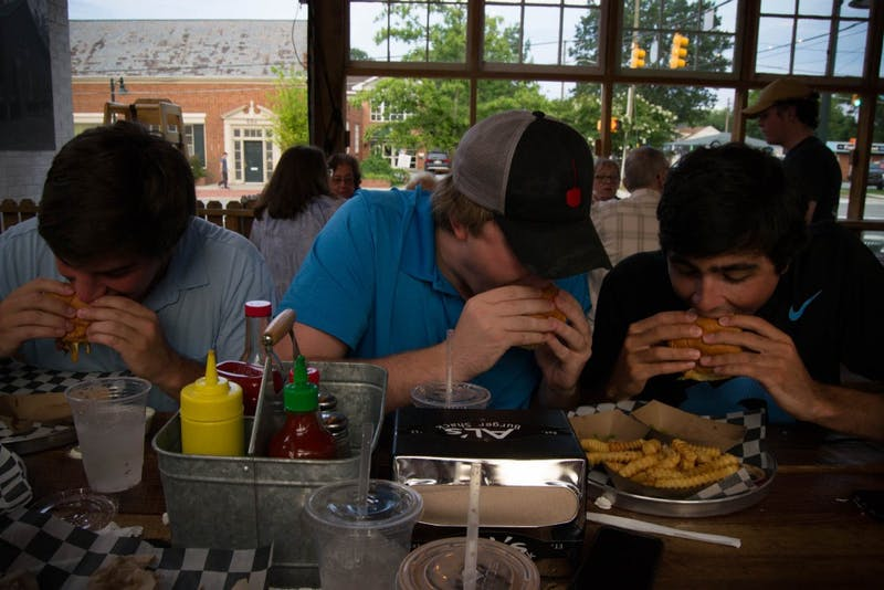 "William Lowe, Mack McMillan and Robbie O'Han take massive bites into their burgers at Al's Burger Shack for dinner. Al's Burger Shack's ""Bobo Chili Cheeseburger"" was voted the Best Burger in America."